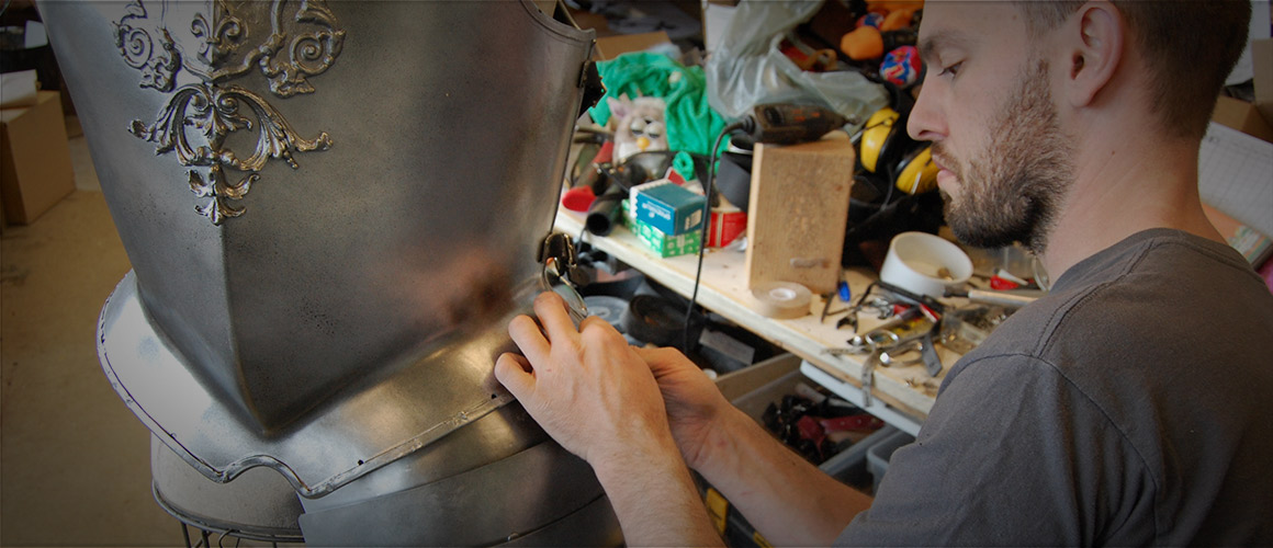 Prop builder Eric Ball works on armour for Camelot.