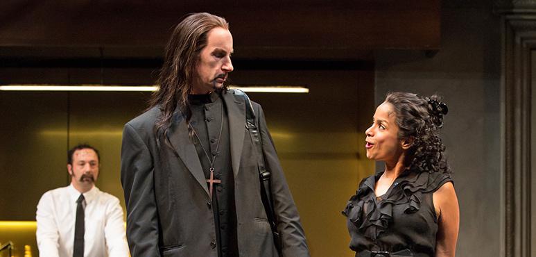 Tom Rooney as Tartuffe and Anusree Roy as Dorine (background: Gordon S. Miller as Laurent). Photography by Cylla von Tiedemann.