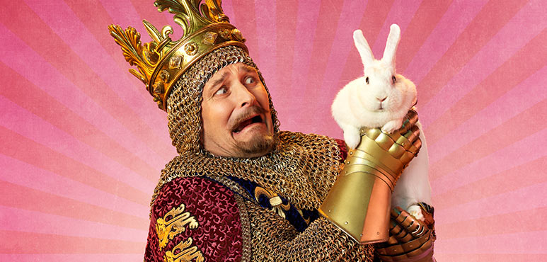 A man dressed as king Arthur, in mail and a crown, holding a bunny rabbit and screaming in fear.