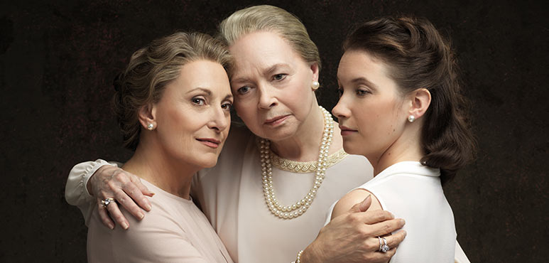 image of three women hugging, ages from elderly to middle aged to late teens.