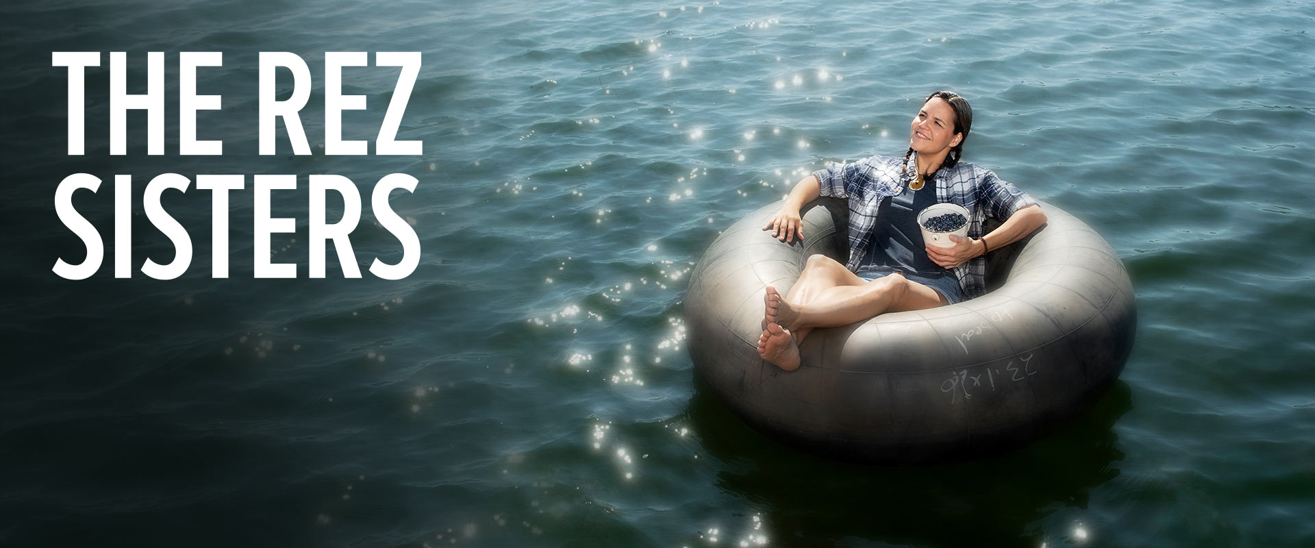 Woman, sitting in an inner tube on the water, eating blueberries from a bucket.