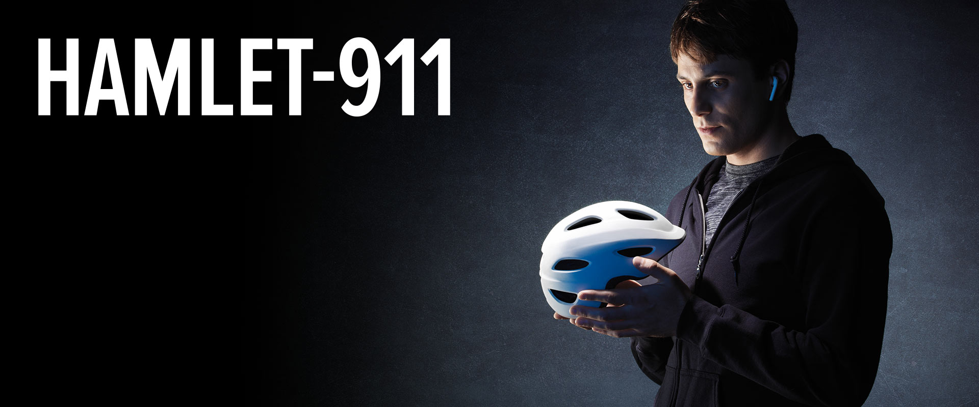 Image of a man holding a white bicycle helmet and staring at it like its a skull
