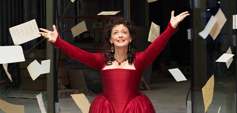 image of a woman, dressed in a Victorian era dress, throwing pages of notes into the air