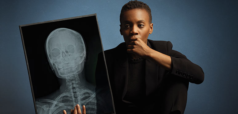 African American woman sitting down, looking at an x-ray of a human head.