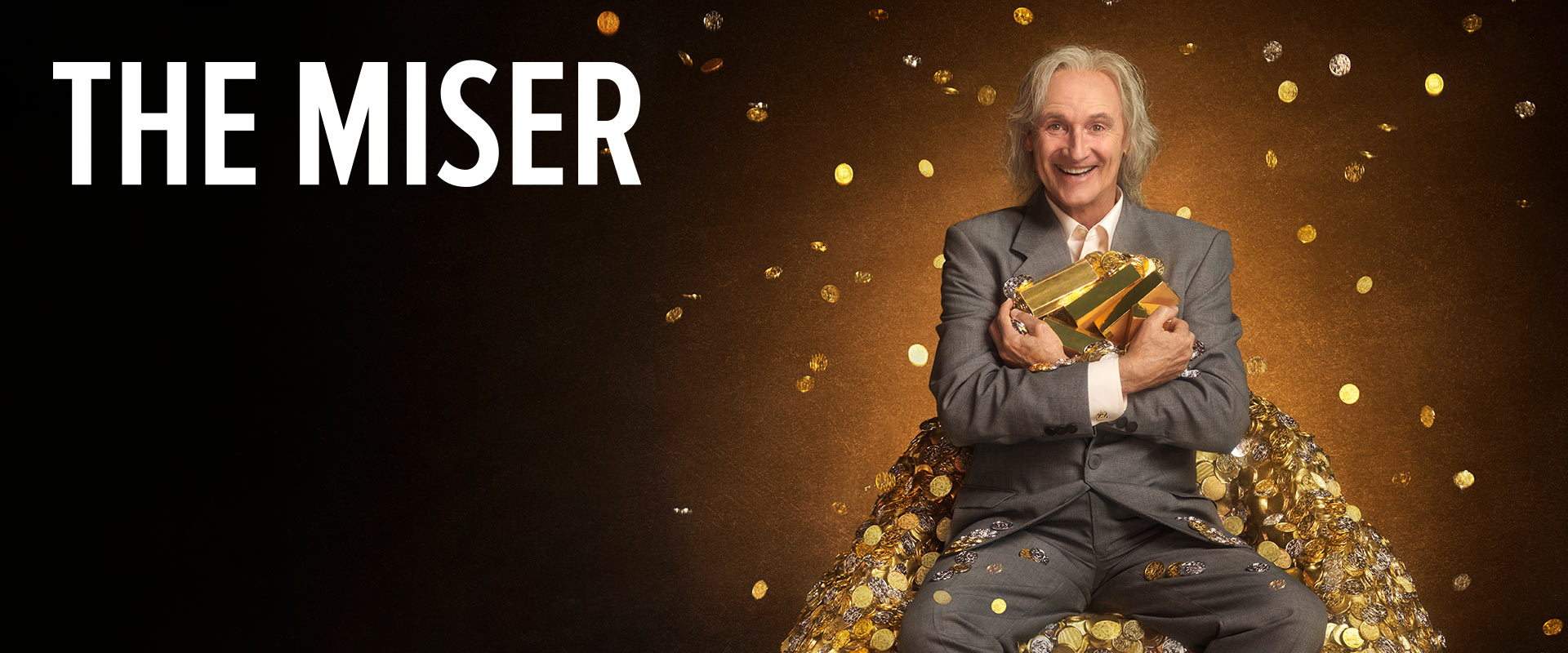 Image of a man in his 60s, sitting on a pile of gold, grinning.