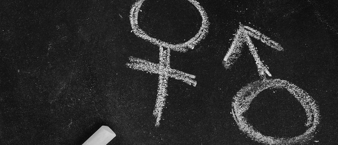 Stock photo of gender symbols written in chalk.