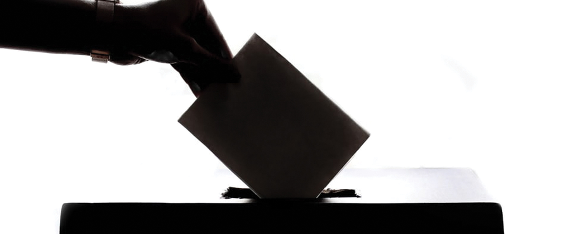 Person putting a voting ballot into a box