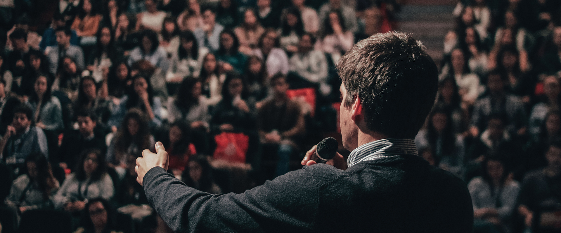 Photo of a man giving a speech in front of an audience