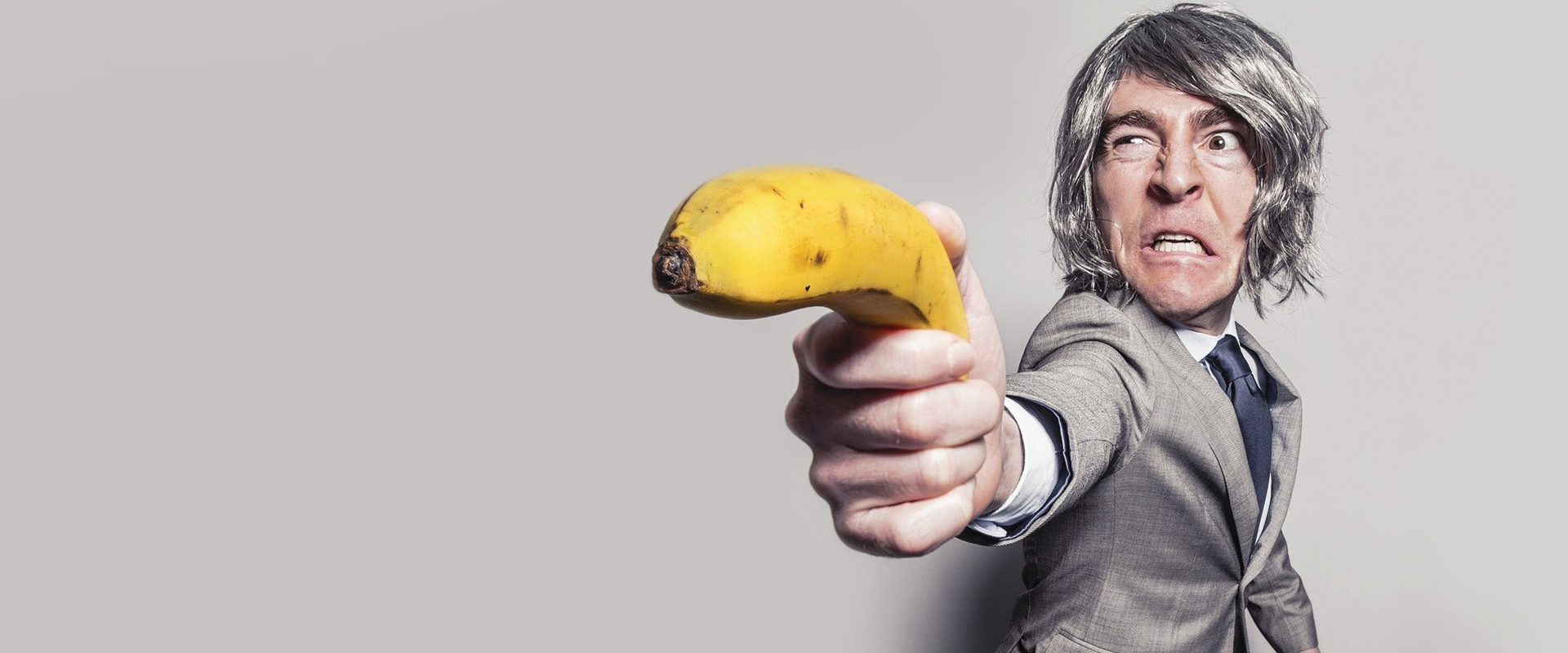 Photo of a man holding a banana like a gun