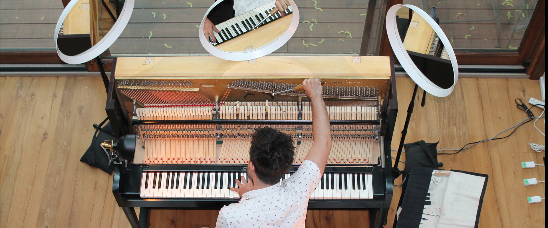 Stock photograph of someone tuning a piano