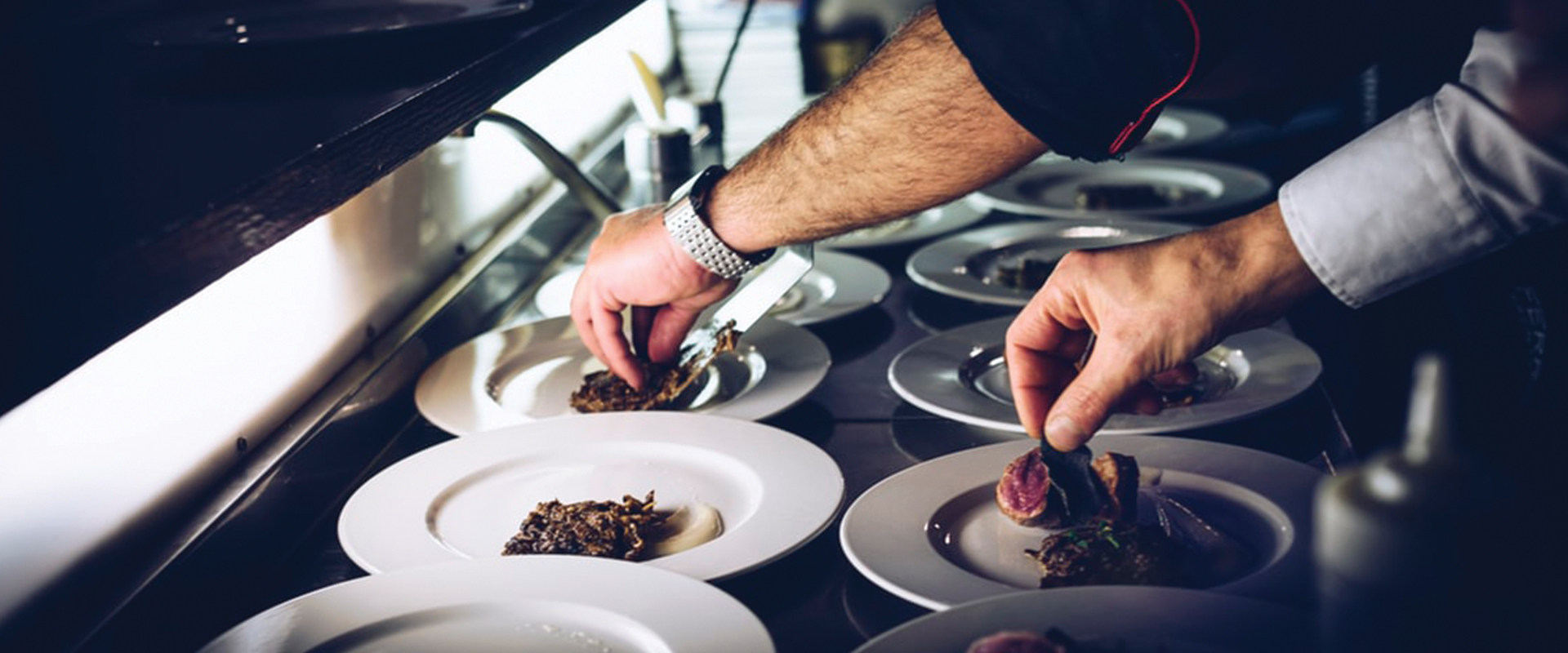 image of chefs arranging food on a plate